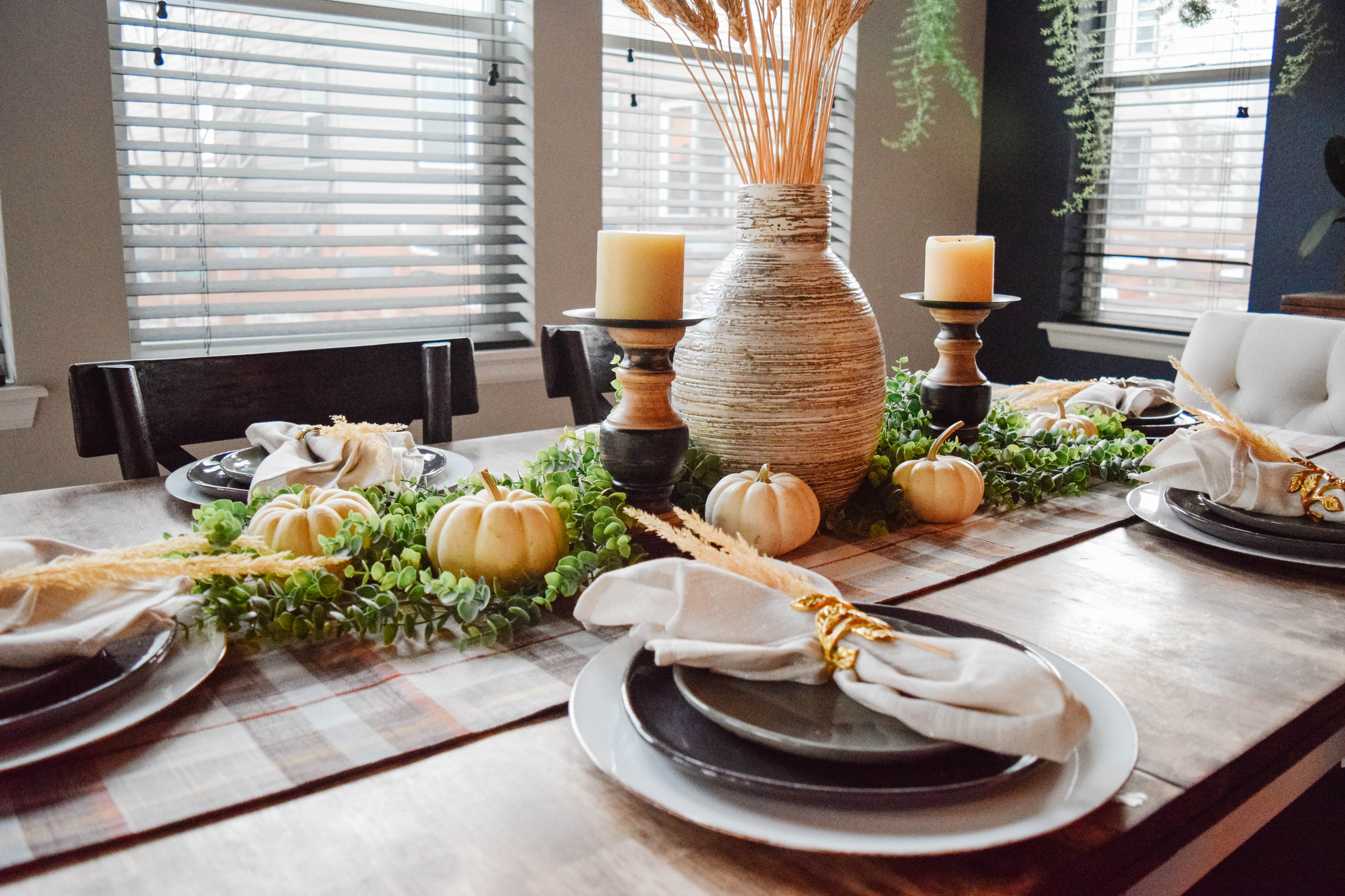 Fall and Thanksgiving Tablescapes with green and wood color scheme, candle sticks and large vase with wheat