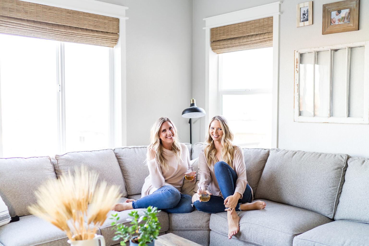 The two authors of the blog sitting on a couch drinking wine.