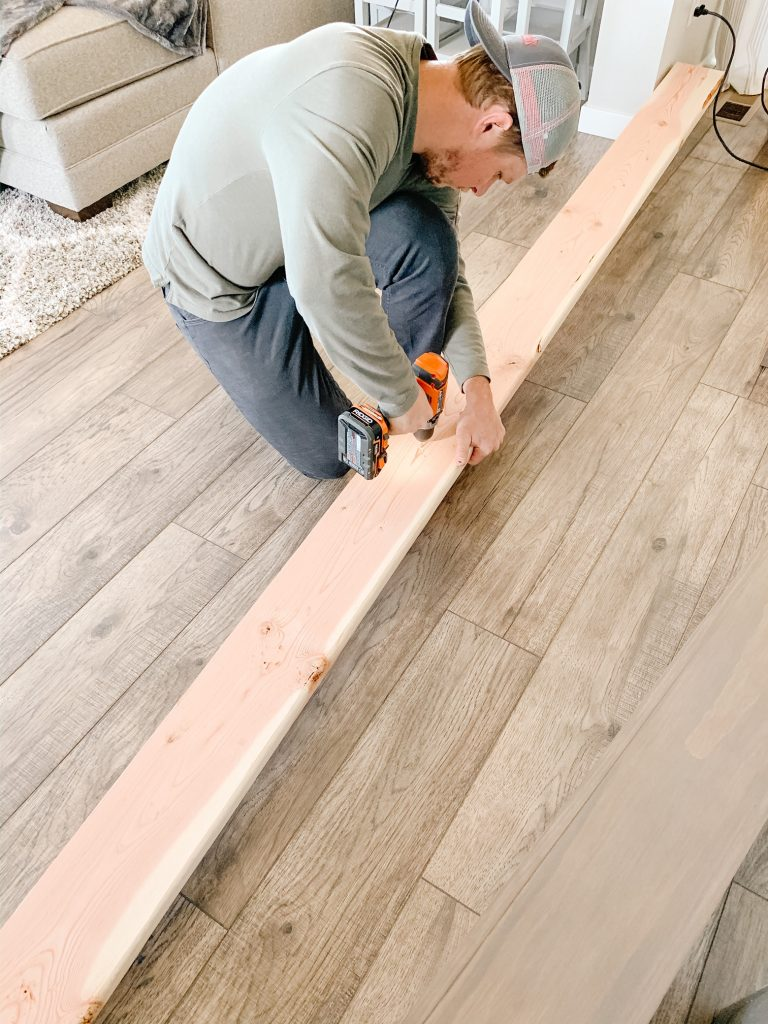man drilling holes into wood board