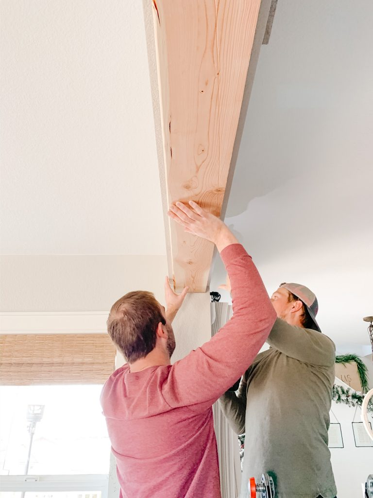 two men screwing in a piece of wood into a ceiling