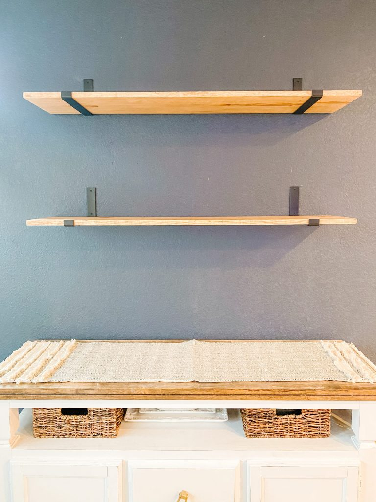 stained wood shelves with black brackets on navy wall