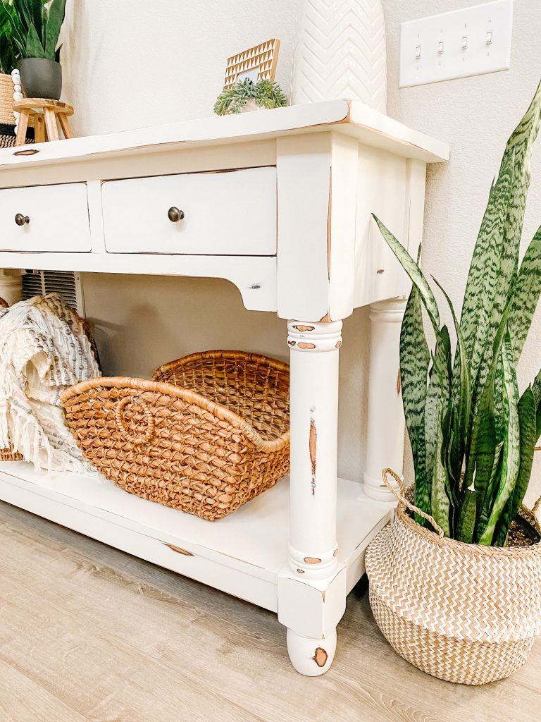 chalk paint console table with baskets below and snake plant in basket