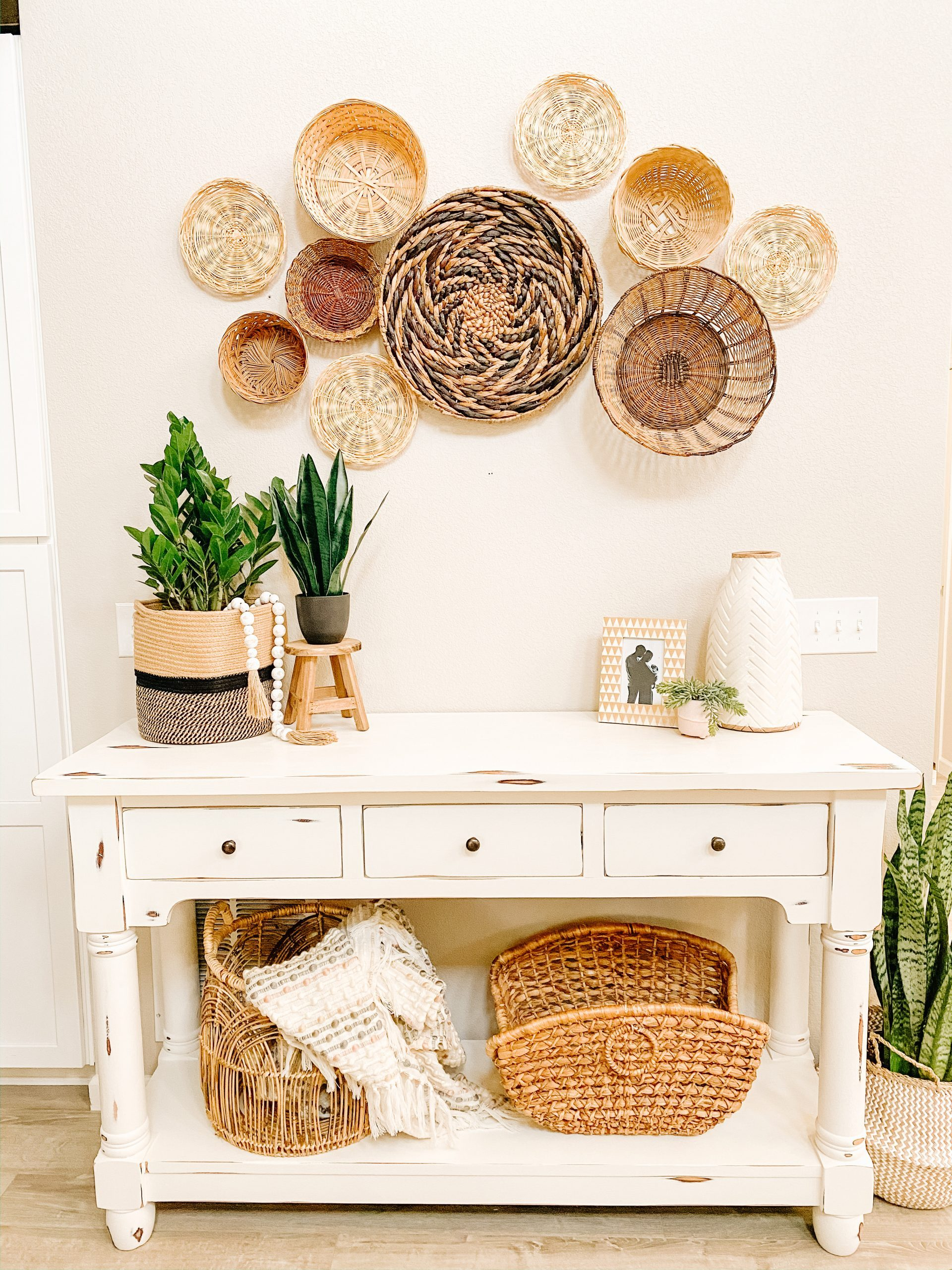 white chalk paint table with vintage basket wall above
