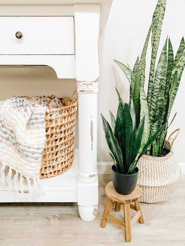 white console table with basket and throw snake plant in basket