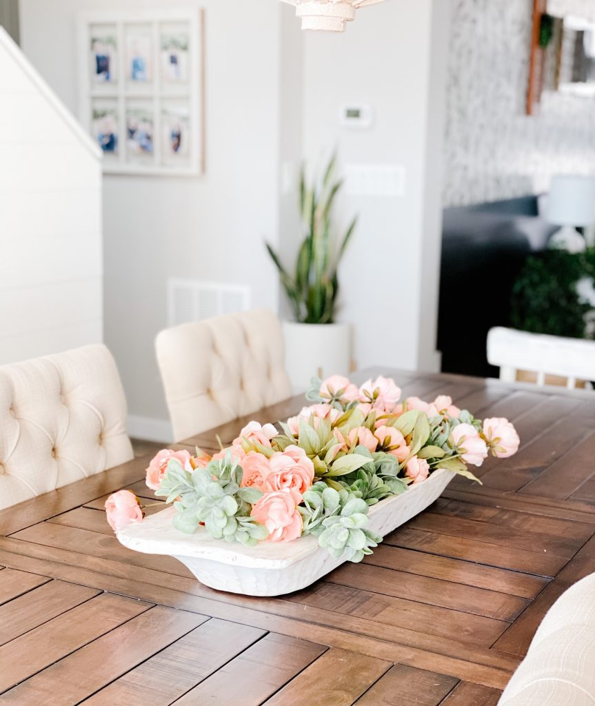 Simple Spring Centerpiece. Faux spring florals and faux greenery in a large antique dough bowl.