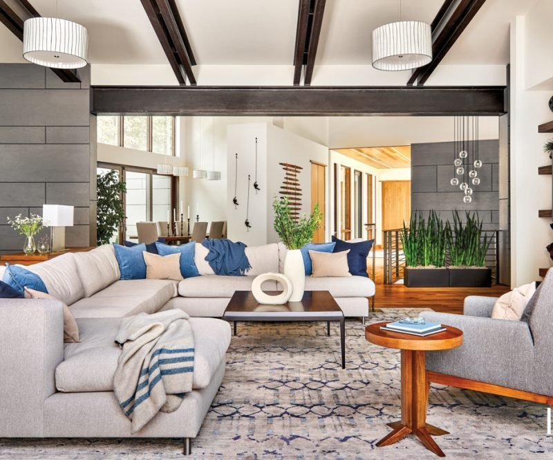 contemporary living room with cool grey and blue tones, large sectional sofa and industrial steel beams at the ceiling