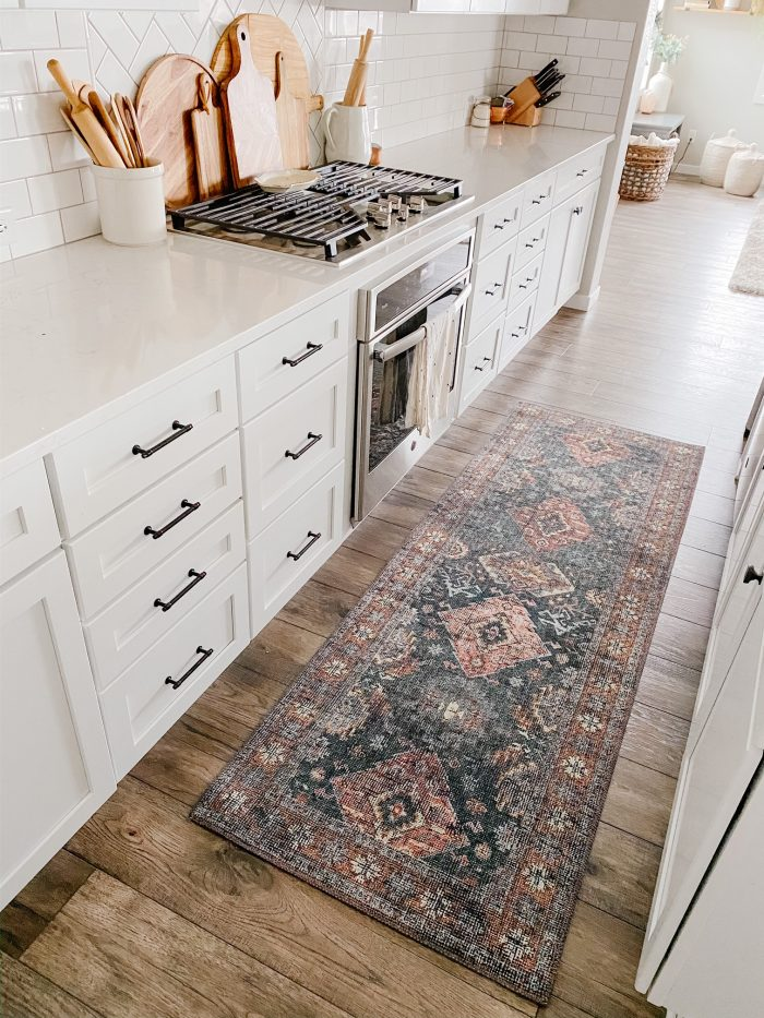 White kitchen cabinets with white quartz counters and a loloi runner rug.