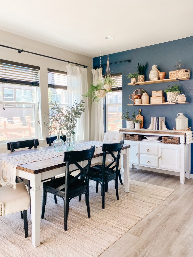 staged home dining room with hale navy accent wall and styled floating shelves