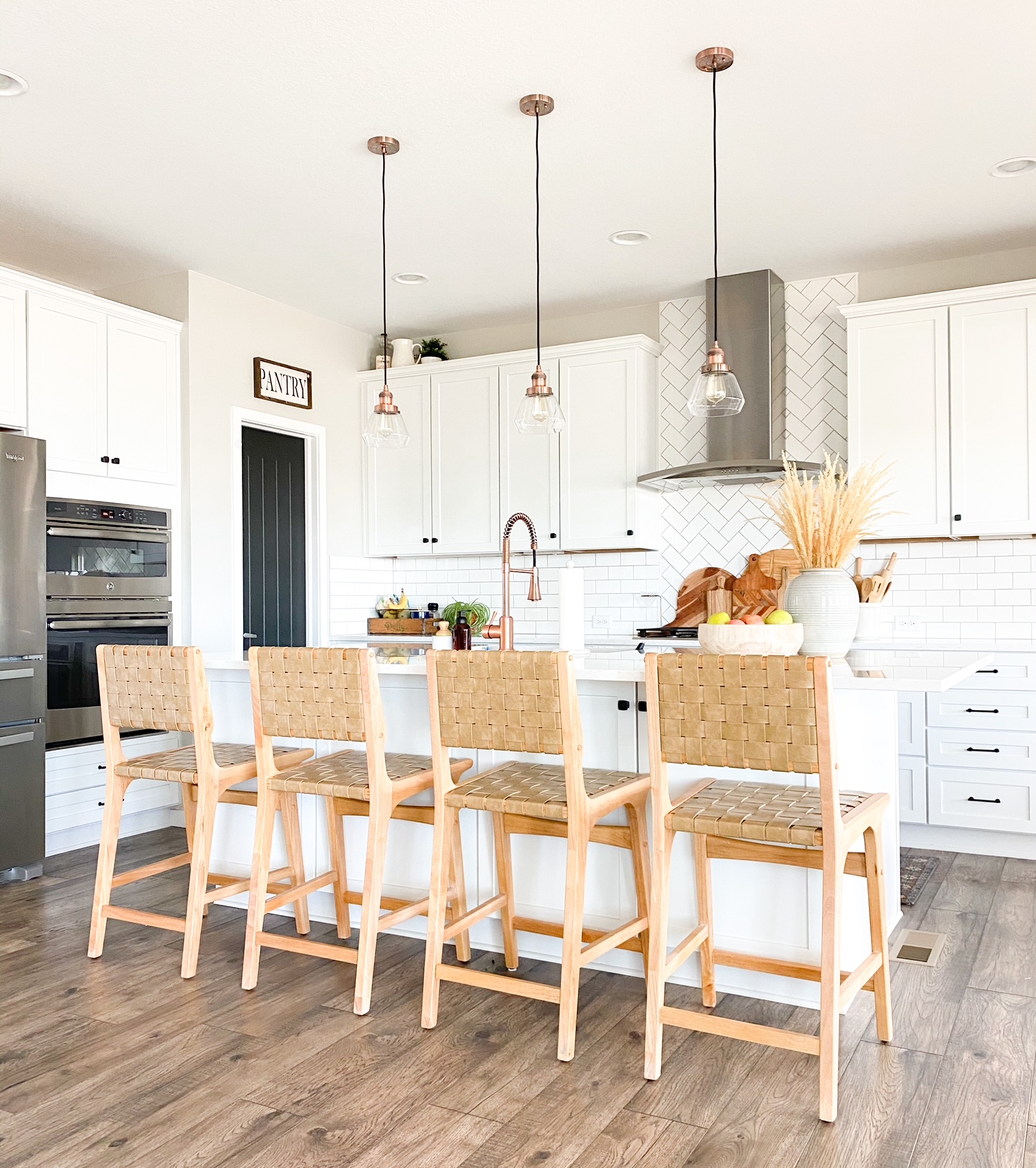 boho bar stools in white kitchen with copper accents