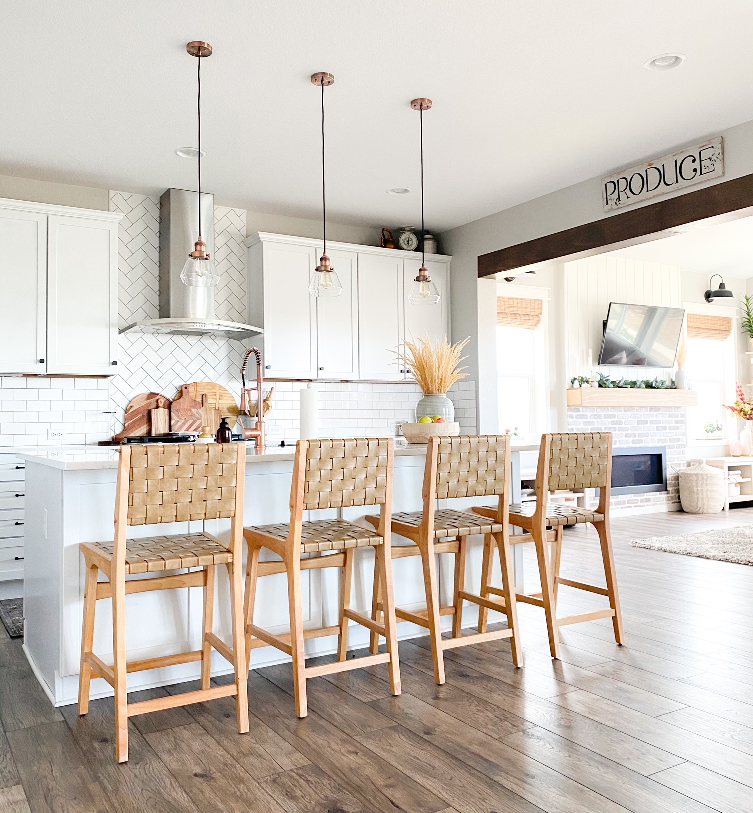 boho bar stools in a white kitchen with  brick and shiplap fireplace in the background