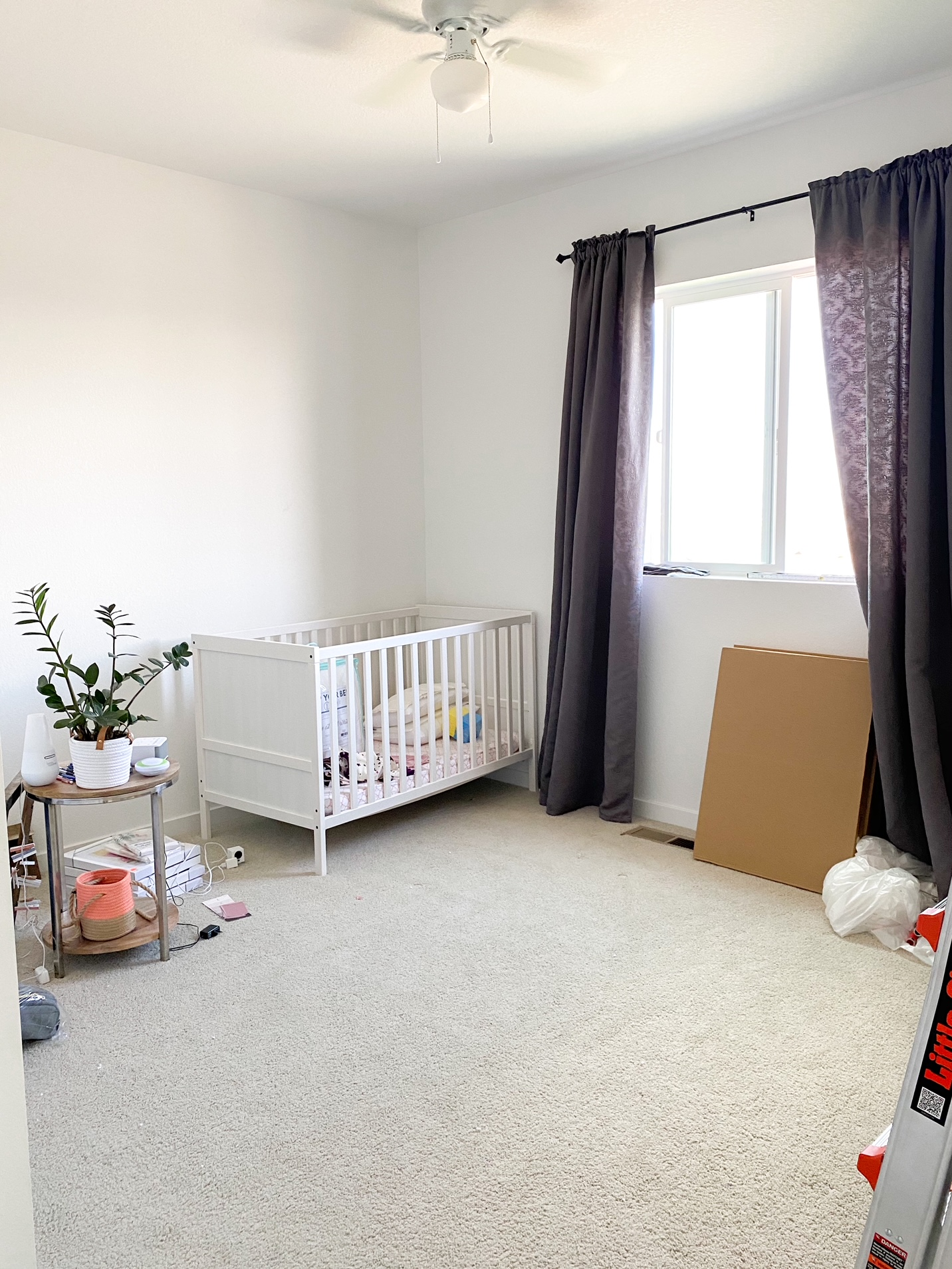 Room with white crib and gray curtains