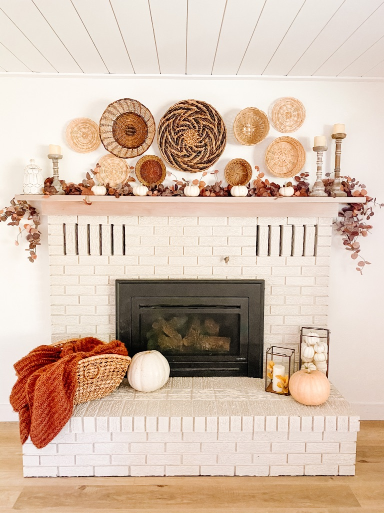 simple fall fireplace mantel with fall garland and white pumpkins