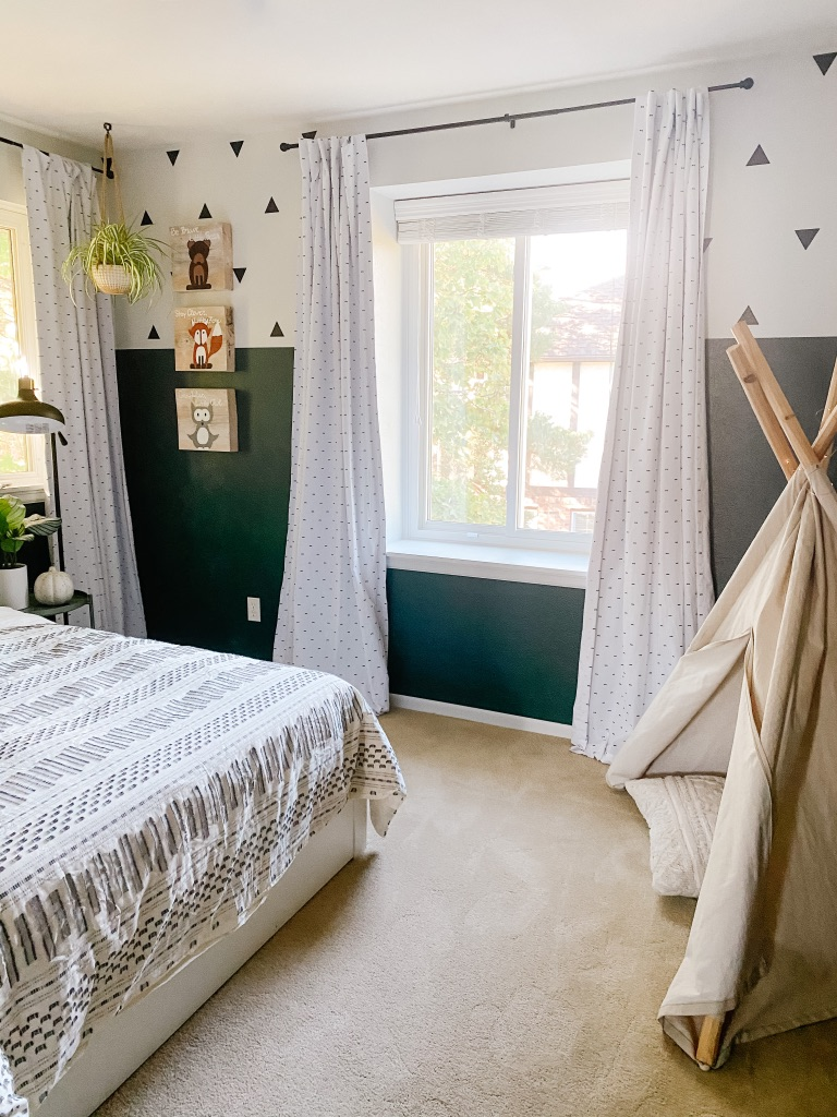 boys boho bedroom idea with colorblock green and white wall and white frame gallery wall