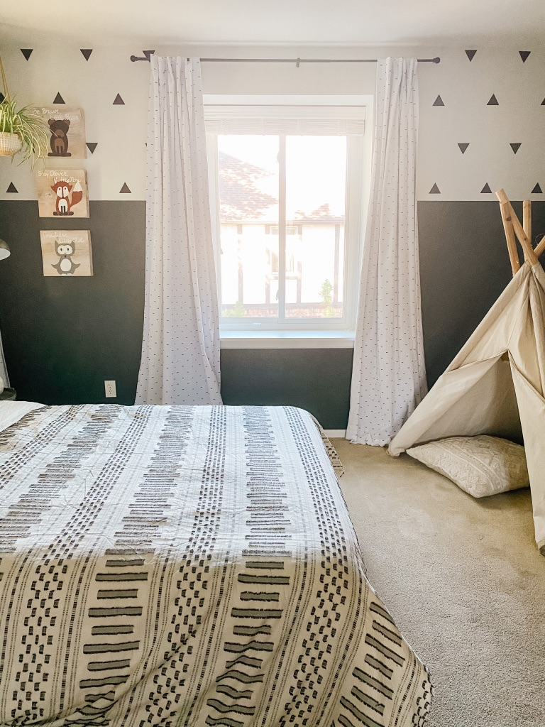 boys boho bedroom idea with colorblock dark green and white wall and black triangle wall decals and teepee