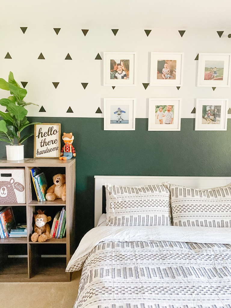 boho toddler room with colorblock dark green and white wall and black triangle wall decals