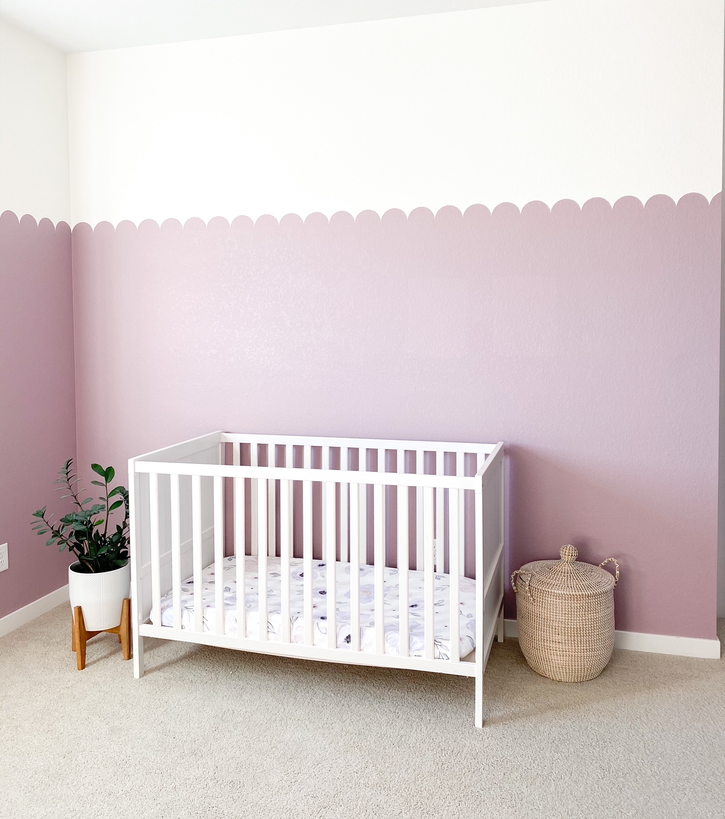 nursery with white crib and purple walls