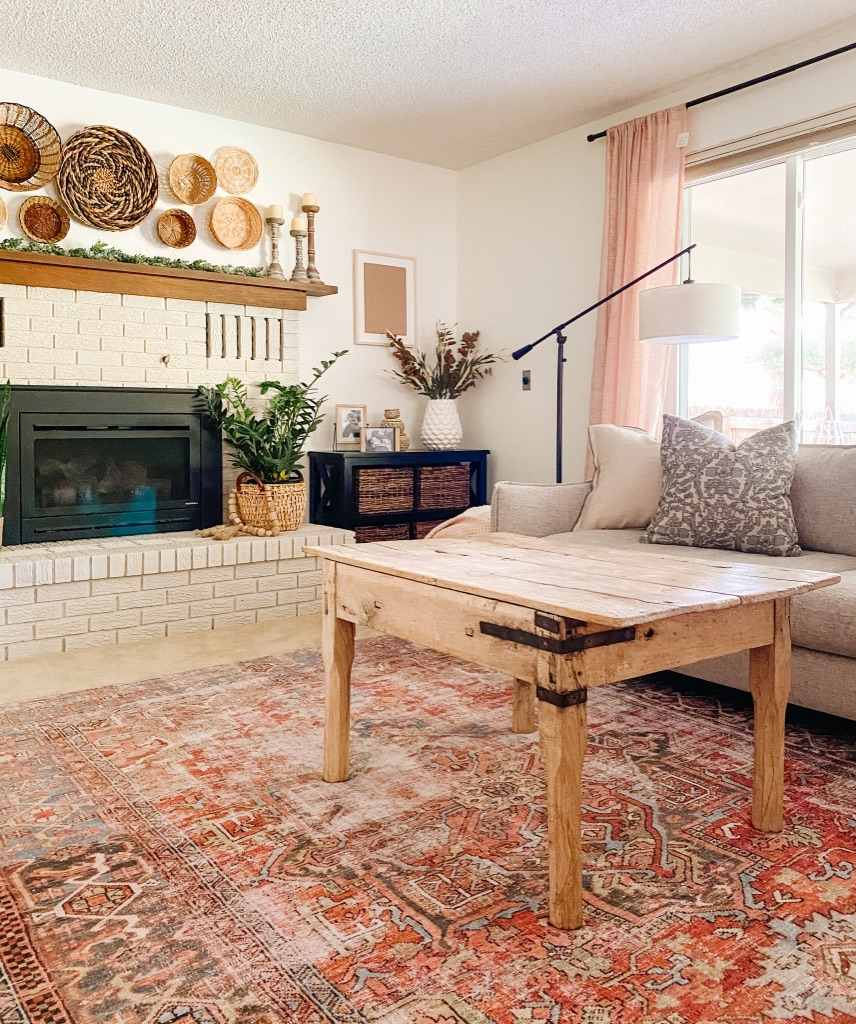 boho living room with brick painted fireplace and boho terracotta area rug from Loloi