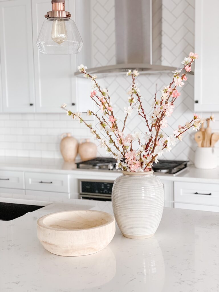 Spring faux blossom stems in a vase in the kitchen is a great way to add color to your neutral home!