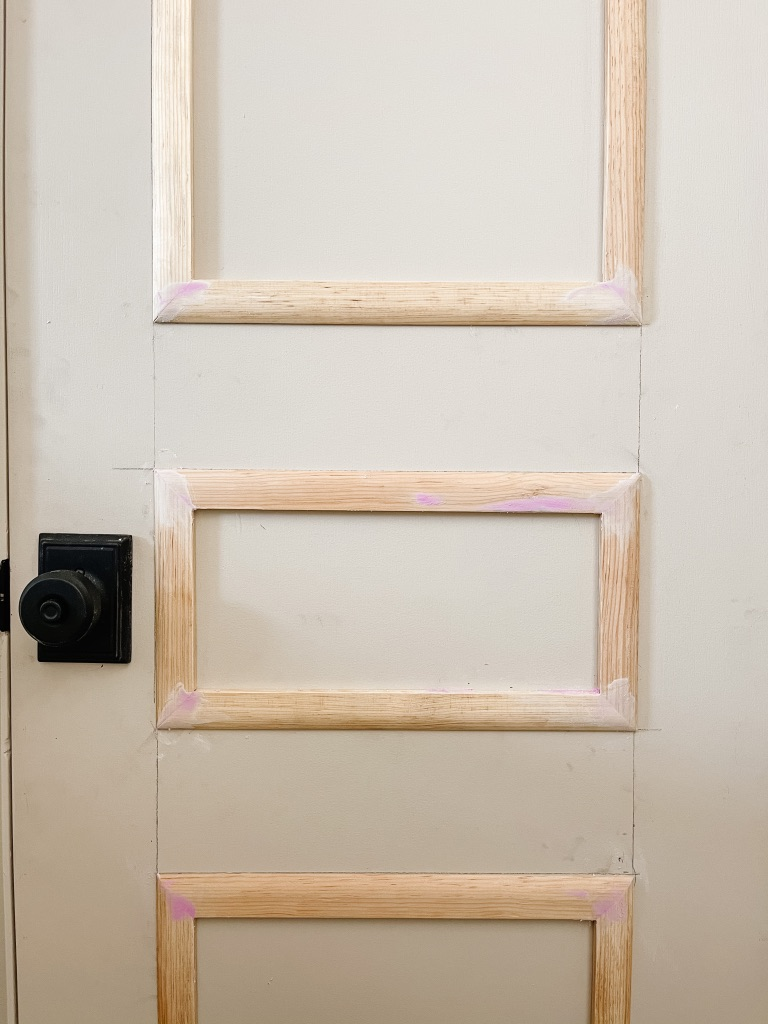 applying wood putty to gaps in wood moulding on flat panel doors