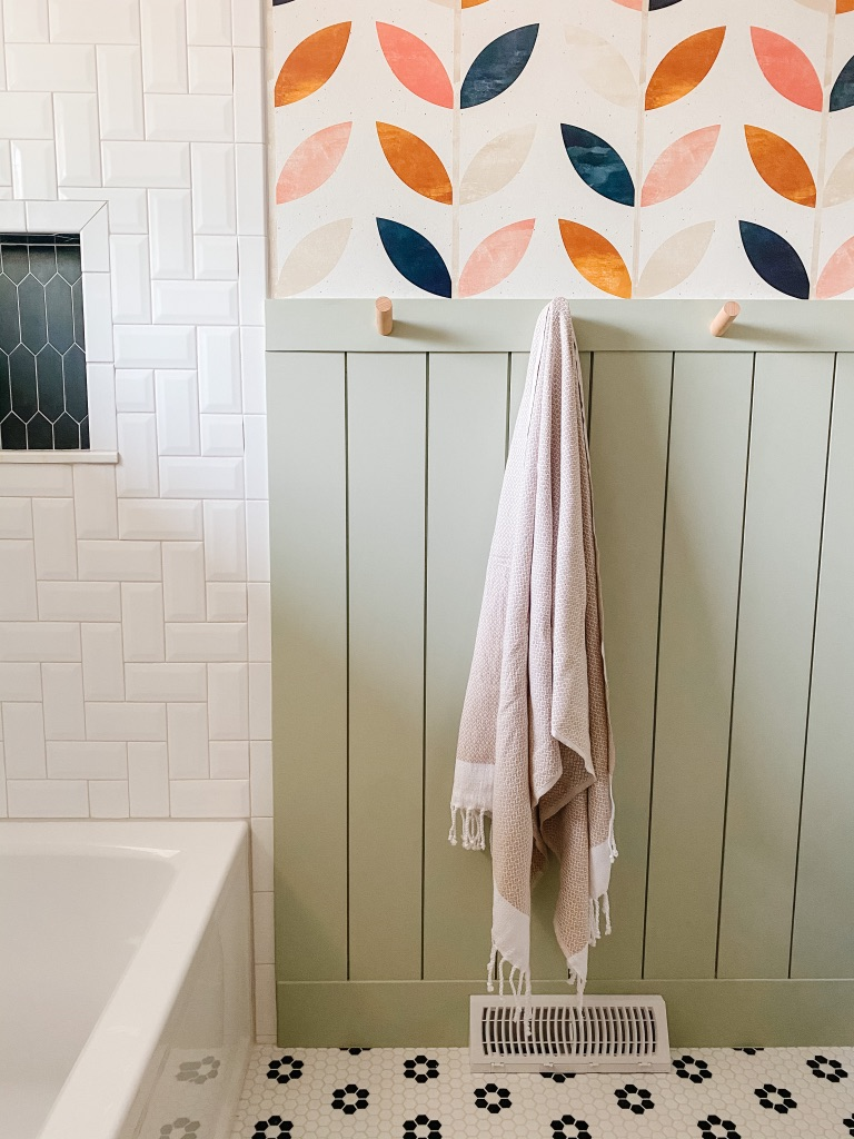 wood peg towel hooks in a colorful bathroom with green shiplap