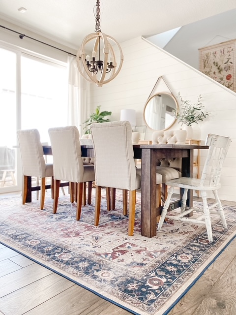 Dining room with farmhouse table, tufted dining chairs and ruggable rug.