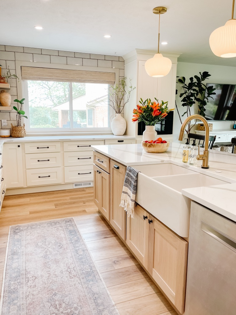 kitchen remodel with large white farmhouse sink and gold faucet and white oak cabinets at island