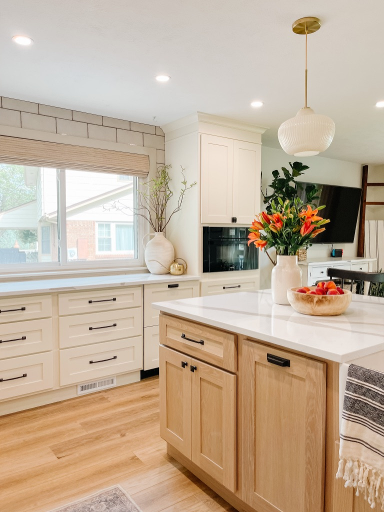 decorate your kitchen countertops with statement pieces like large vases with greenery and faux stems, and a big wooden bowl for fruit