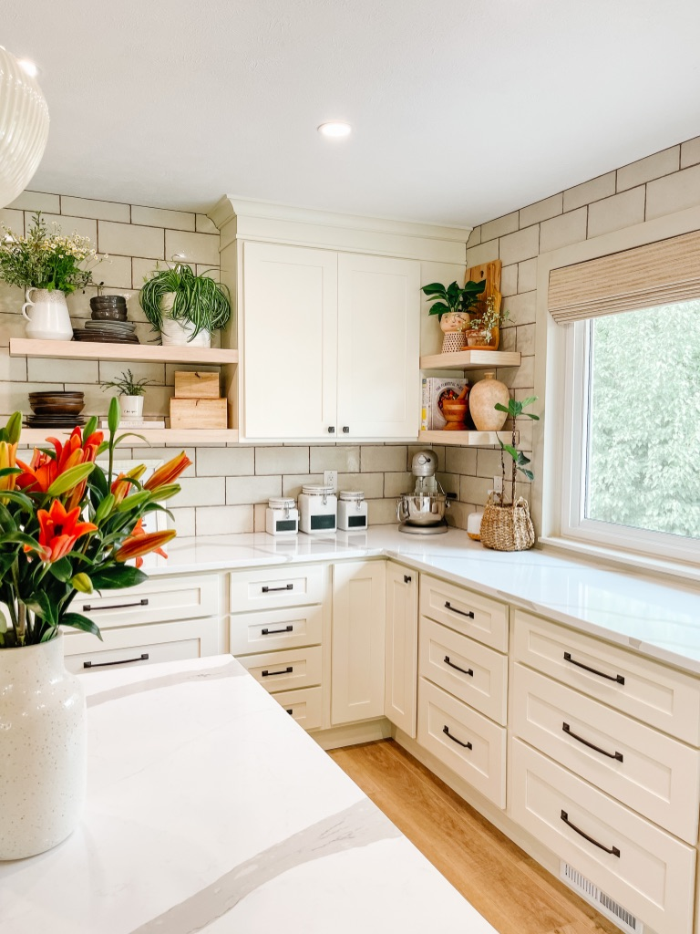 off white kitchen cabinets with white oak opening shelving at the corner and lots of drawers at the lower cabinets