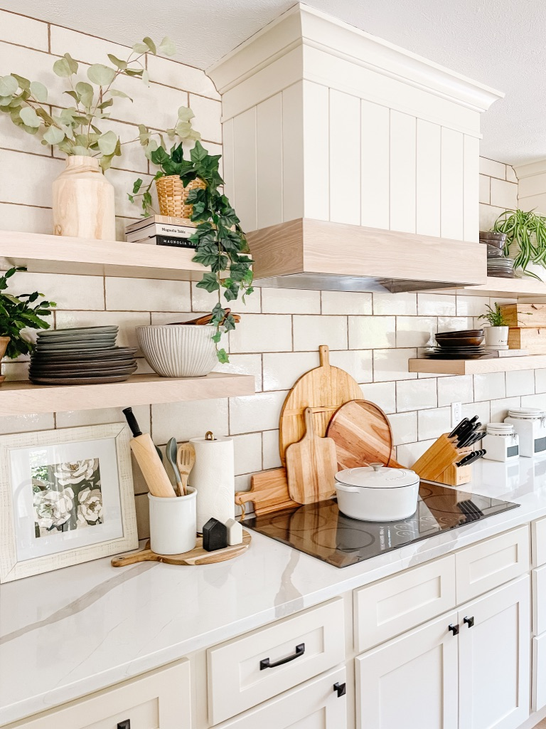 style your kitchen stove area by layering large wooden cutting boards behind your cooktop and add a white dutch oven
