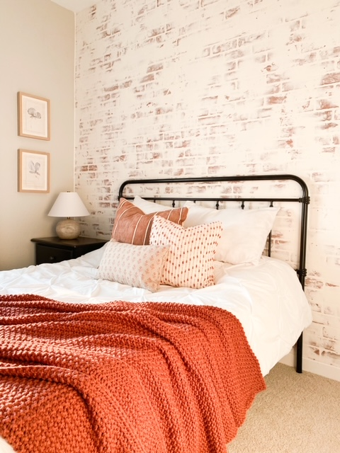 Fall decor in bedroom with white washed brick wall.