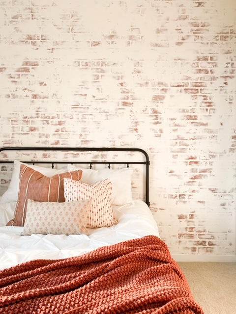 White washed brick wall in bedroom.