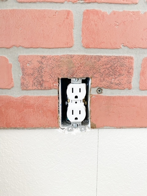 How to cut around the edges of an outlet with a faux brick panel.