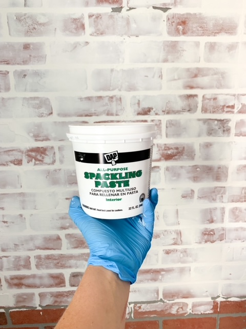 Using spackling paste on faux brick panels.
