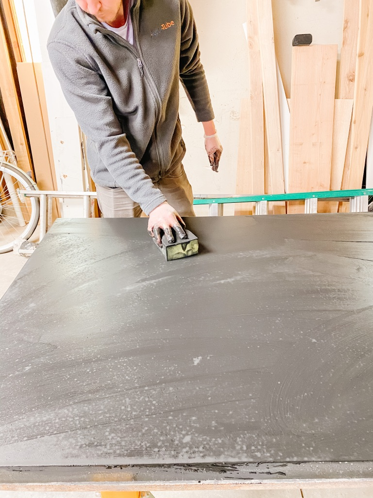 Filling holes in black DIY Concrete Dining Table with Z Counter-Patch slurry mixture