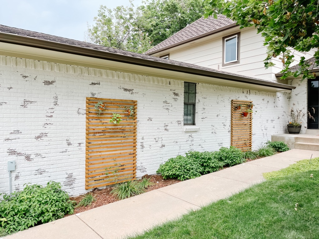 easy DIY slatted wood trellises against a white brick wall with hanging terra cotta pots with vines