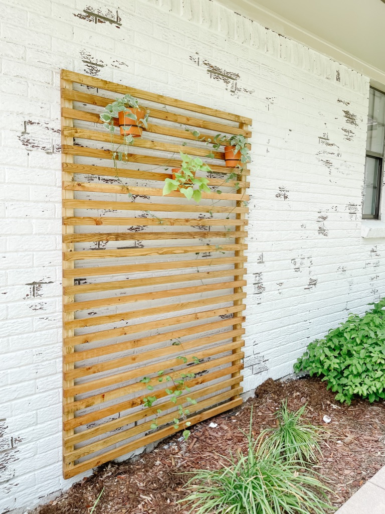 simple and affordable wood slat trellis against german schmear white brick with hanging planters and vinca vines
