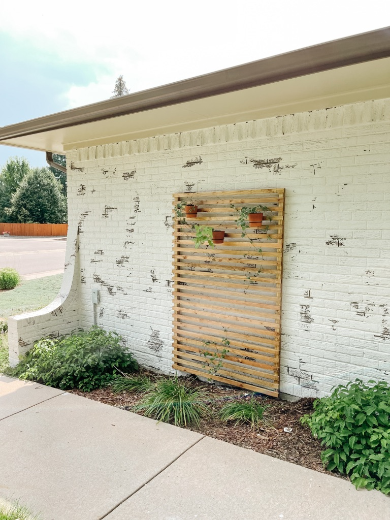simple and affordable wood slat trellis against german schmear white brick