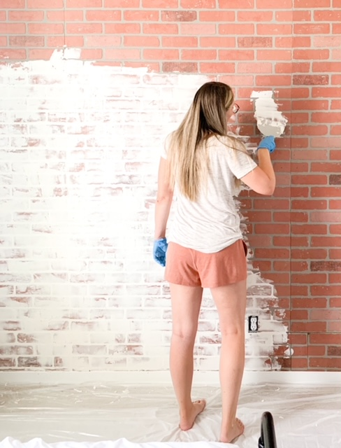 Spreading on spackling paste on a  faux brick wall.