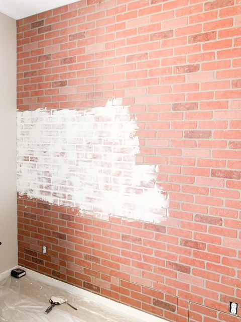 Wall of brick paneling with spackling paste.