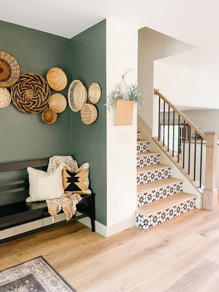 colorful peel and stick wallpaper at stair risers and dark green accent wall with black bench and wall baskets