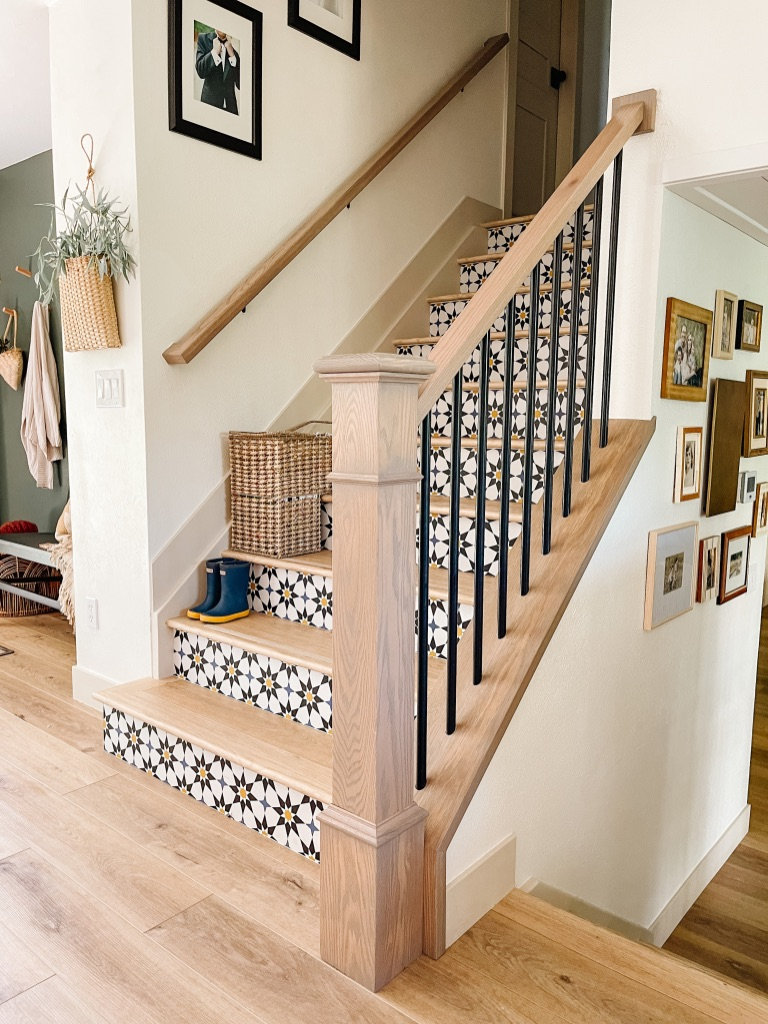 diy peel and stick wallpaper at stair risers with updated stair railing with white oak hand rail and black metal balusters