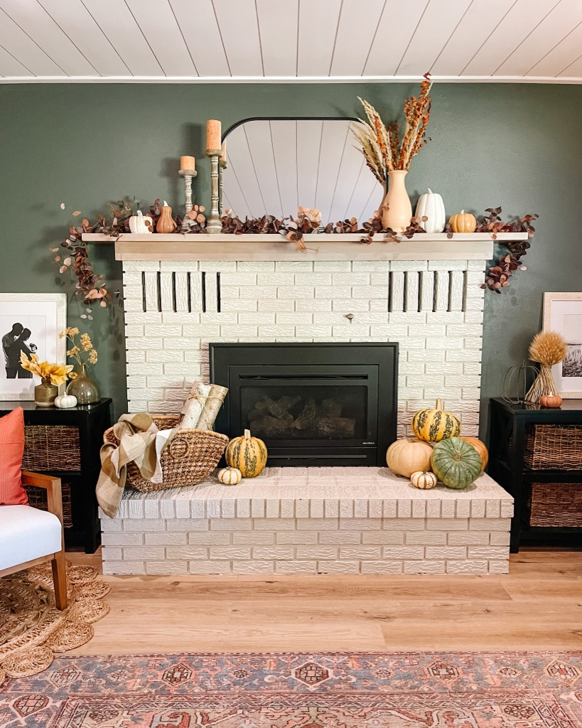 simple fall home decor ideas with moody dark green wall with painted brick fireplace