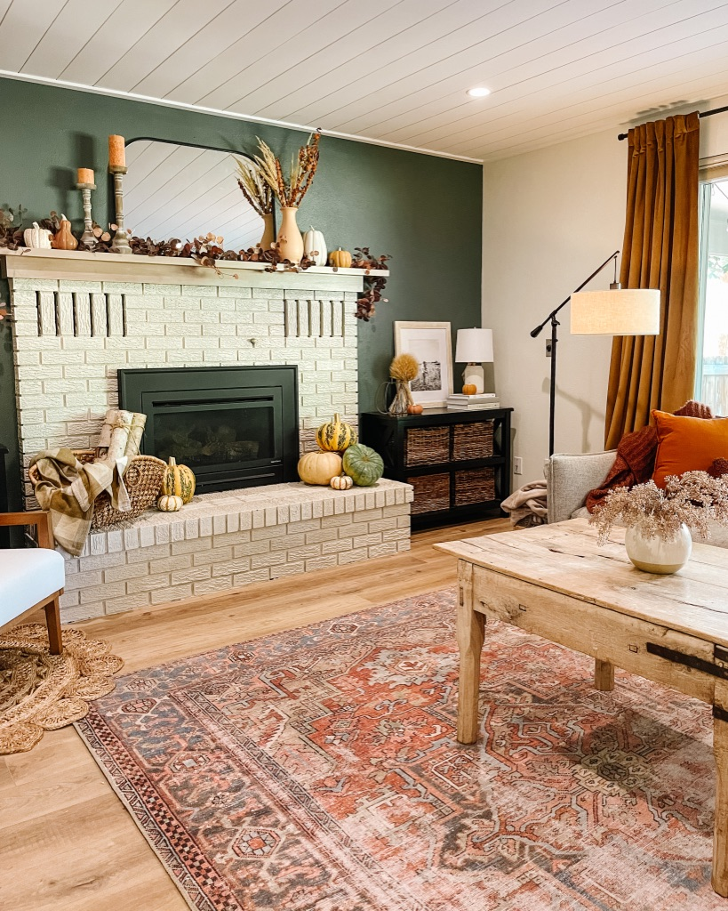 terracotta loloi rug in living room with cozy fall decor with moody dark green accent wall and white painted brick fireplace